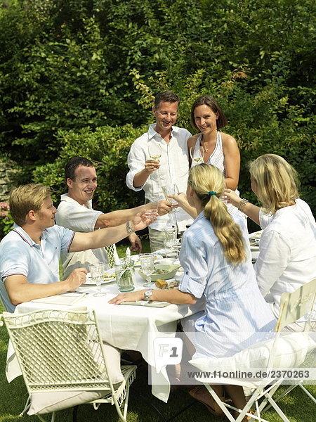 Gruppe von Menschen essen im Garten