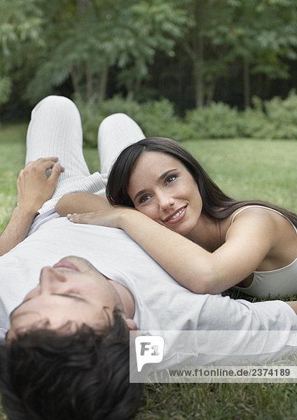Paar auf Gras zusammen lächelnd Außenaufnahme liegend