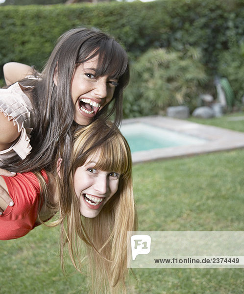 Woman outdoors giving other woman piggyback ride and smiling