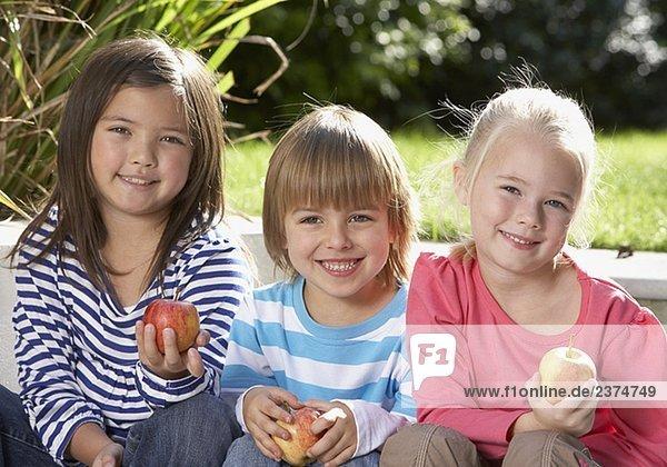 Außenaufnahme sitzend lächeln halten jung 3 Apfel freie Natur