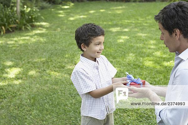 Geschenk Außenaufnahme Mann geben lächeln Junge - Person jung freie Natur