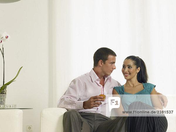 Paar sitzend auf der Couch mit Kuchen