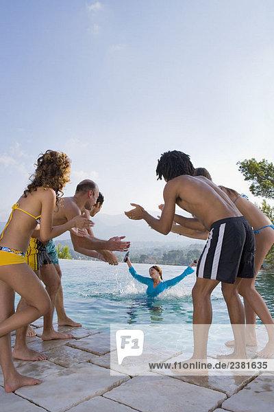 Männer und Frauen werfen einen Freund in einen Pool.