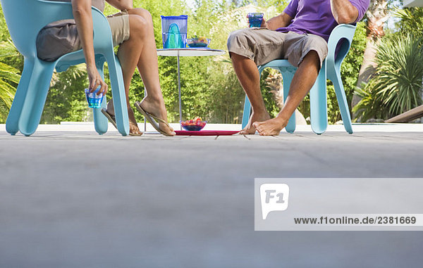 Ehepaar auf einer Holzterrasse am Pool