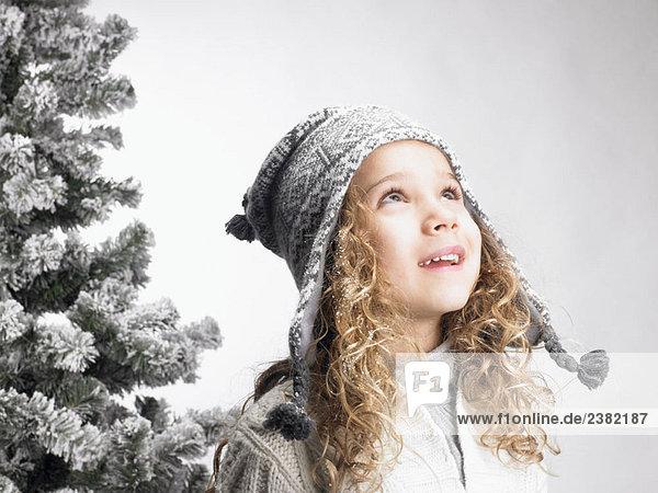 Little girl next to a fir-tree