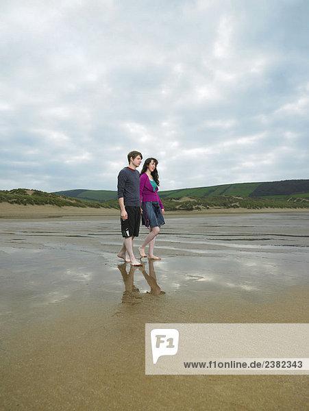 Junges Paar beim Spaziergang am Strand