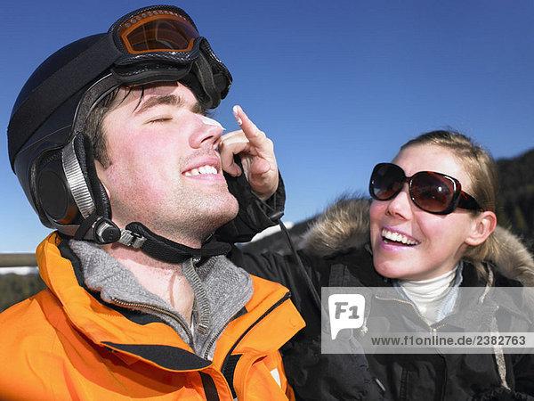 Junge Frau  die Sonnencreme auf einen Freund aufträgt