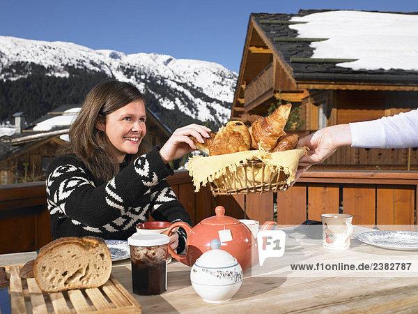 Junge Frau beim Frühstück auf der Terrasse