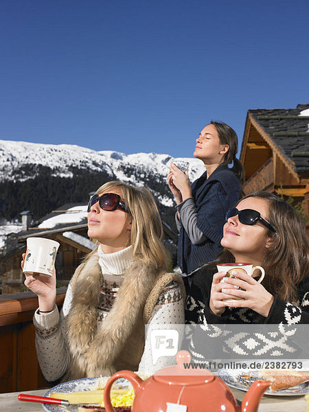 Junge Frauen beim Frühstück auf der Terrasse