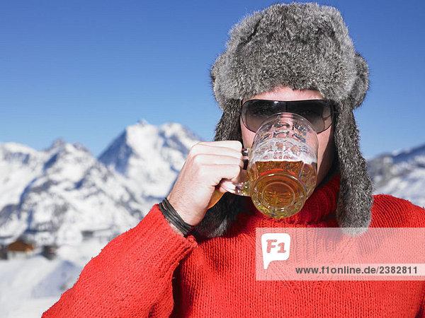 Junger Mann beim Trinken in den Bergen