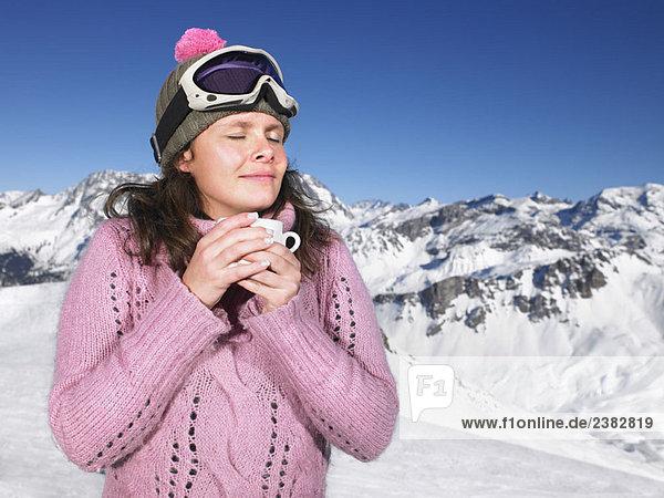 Junge Frau beim Trinken in den Bergen