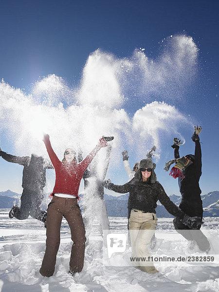 Gruppe wirft Schneebälle in die Luft