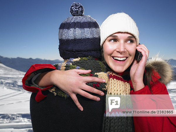 Mann umarmt Frau am Telefon