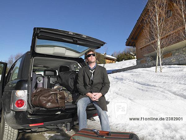 Junger Mann vor gepacktem Auto