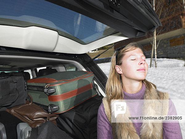 Junge Frau vor gepacktem Auto