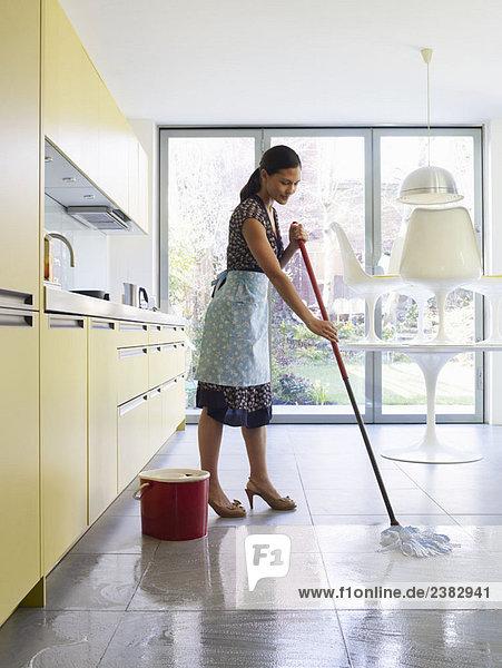 Junge Frau beim Wischen des Küchenbodens