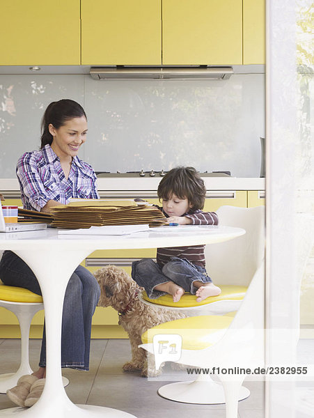 Woman working at home  with son at table