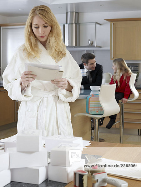 Frau liest Post im Morgenmantel