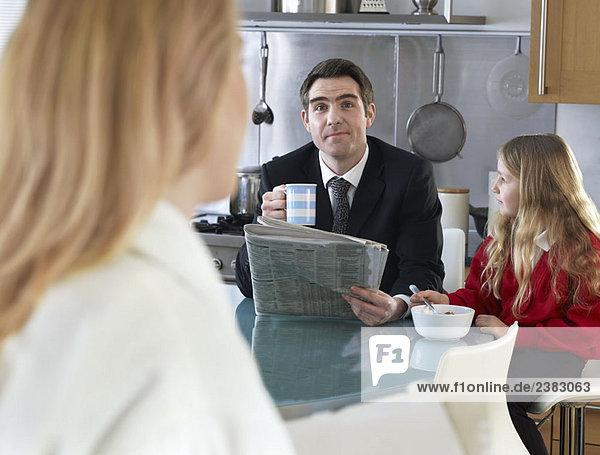 Mann am Frühstückstisch mit Tochter