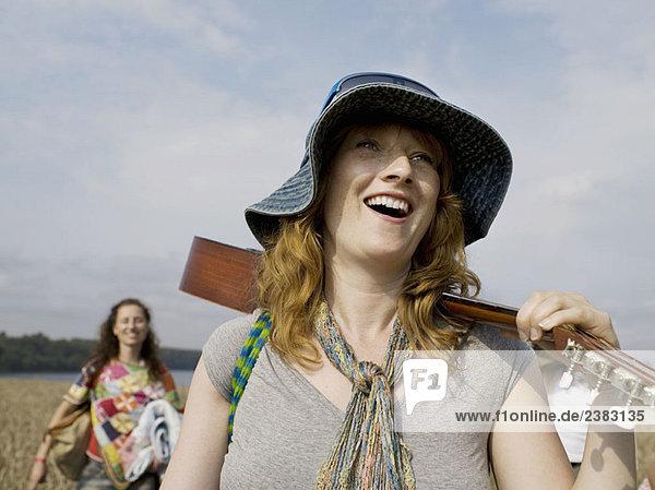 Frau läuft mit Gitarre auf der Schulter