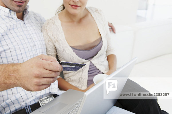 Couple on sofa  making purchase online