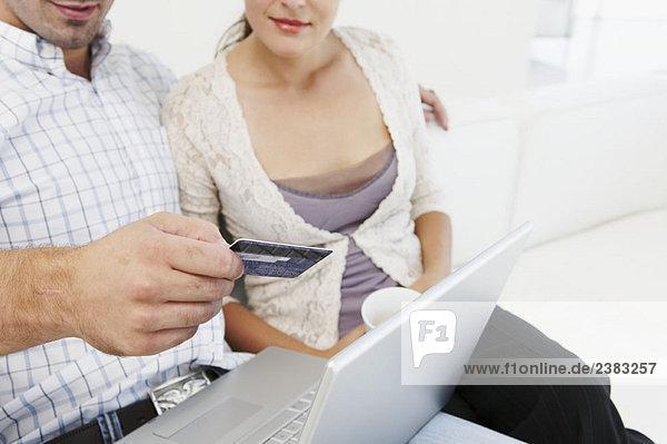 Paar auf dem Sofa  kauft online ein