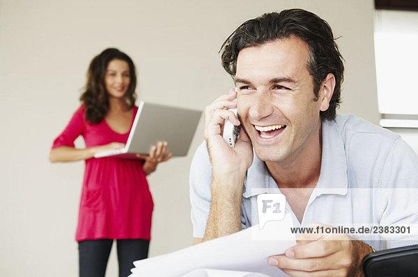 Lächelnder Mann am Telefon mit Rechnungen