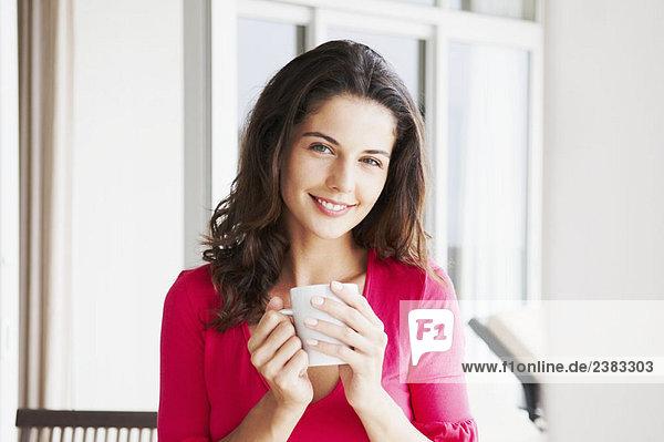 Zufriedene Frau hält Tasse