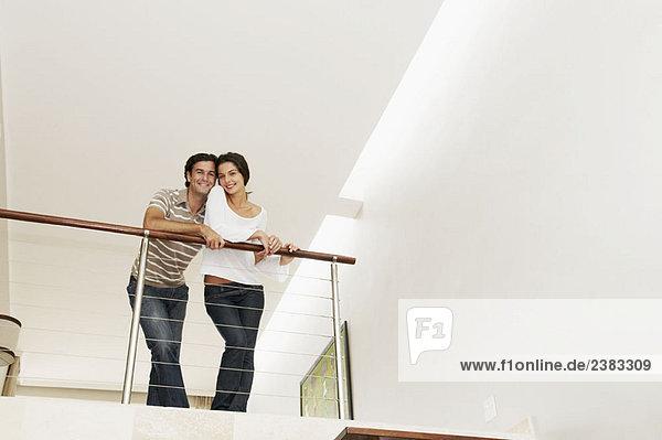 Zufriedenes Paar lehnt sich über den Balkon
