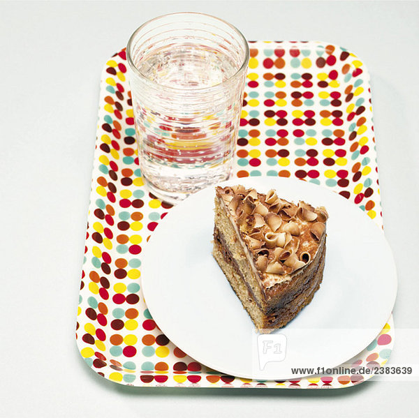 Ein Glas Wasser und ein Stück Torte auf einem Tablett