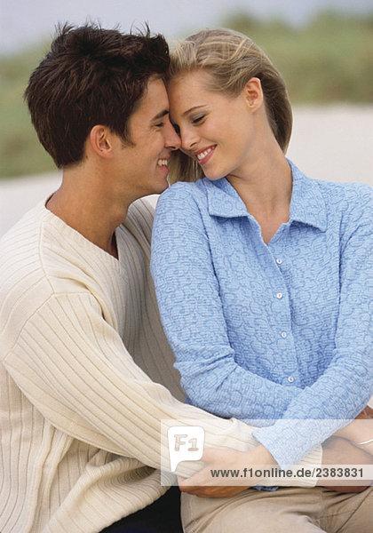 Junges Paar umarmt sich und lächelt sich an