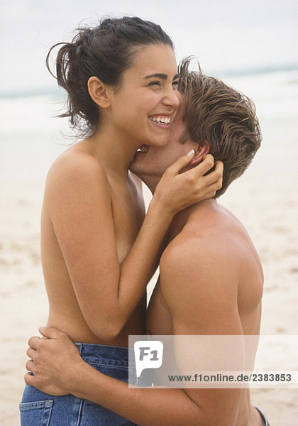Topless young couple embracing each other at beach