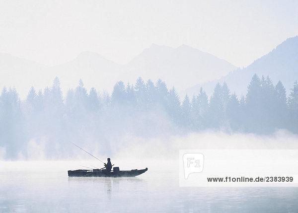 Angler im Morgennebel auf einem See