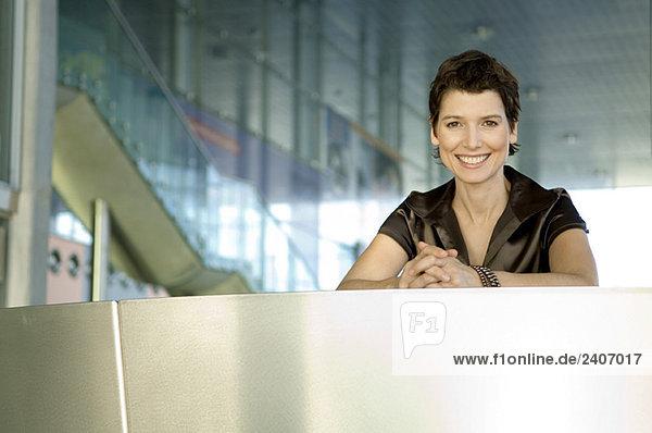 Porträt einer mittleren erwachsenen Frau an einer Hotelrezeption