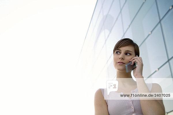 Niederwinkelansicht einer jungen Frau  die auf einem Handy spricht