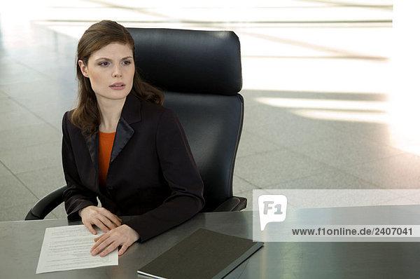 Geschäftsfrau sitzt am Schreibtisch im Büro