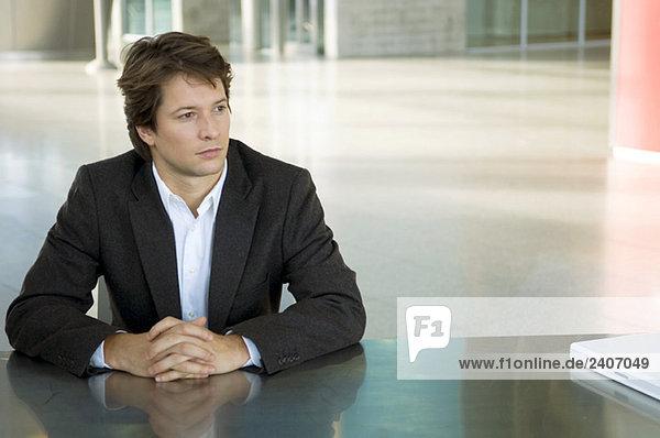 Geschäftsmann am Schreibtisch sitzend mit gefesselten Händen