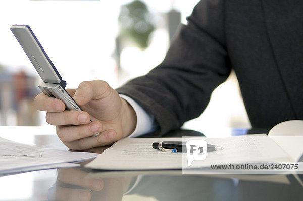 Mittelteilansicht eines Geschäftsmannes mit einem Mobiltelefon