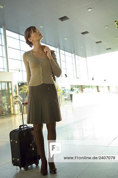 Geschäftsfrau  die mit ihrem Gepäck in einer Flughafenlounge steht.