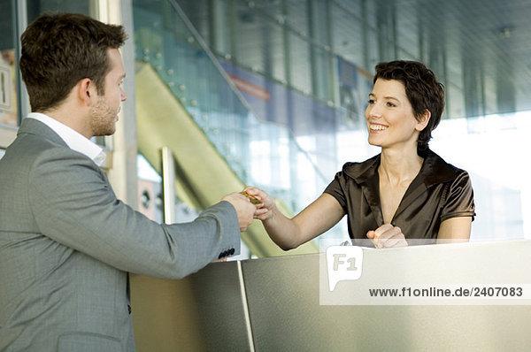 Geschäftsmann  der einer Hotelrezeption eine Kreditkarte übergibt Geschäftsmann, der einer Hotelrezeption eine Kreditkarte übergibt