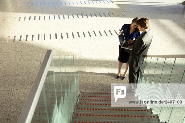Hochwinkelansicht eines Geschäftsmannes und einer Geschäftsfrau mit Laptop