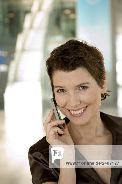 Mittlere erwachsene Frau spricht auf einem Handy