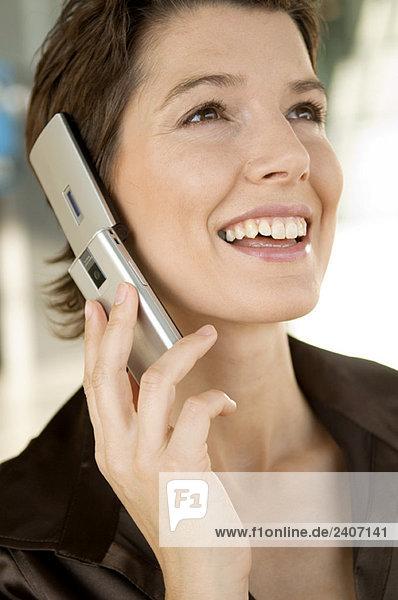 Nahaufnahme einer erwachsenen Frau  die auf einem Mobiltelefon spricht.