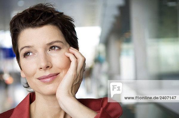 Nahaufnahme einer erwachsenen Frau  die mit der Hand am Kinn lächelt.