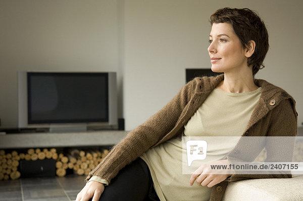 Mittlere erwachsene Frau  die sich gegen eine Couch lehnt. Mittlere erwachsene Frau, die sich gegen eine Couch lehnt.
