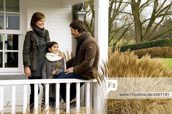 Mädchen mit ihren Eltern lächelnd auf dem Balkon