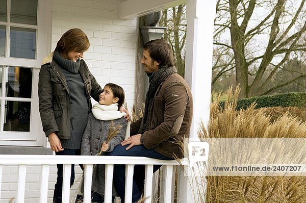 Mädchen stehend und lächelnd mit ihren Eltern auf dem Balkon