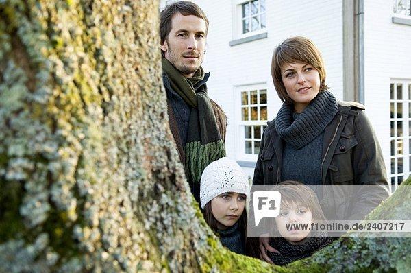Zwei Kinder  die mit ihren Eltern in der Nähe eines Baumes stehen.