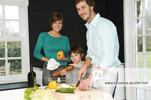 Ein erwachsener Mann und eine junge Frau  die mit ihrem Sohn Essen zubereiten.