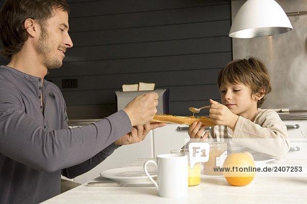 Mittlerer Erwachsener Mann und sein Sohn beim Frühstücken Mittlerer Erwachsener Mann und sein Sohn beim Frühstücken
